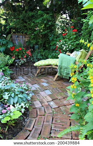 Comfortable lounge chair in a small private garden. Also available in horizontal.  - stock photo