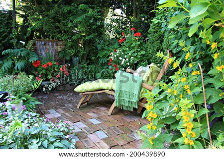 Comfortable lounge chair in a small private garden. Also available in vertical.  - stock photo