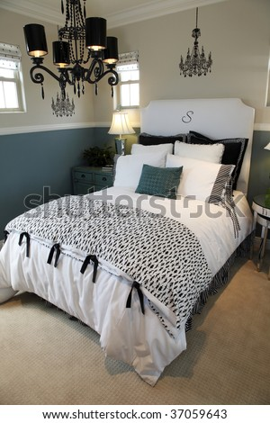 Comfortable modern bedroom with a chandelier. - stock photo