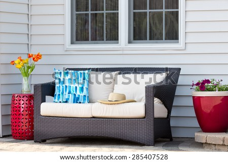 Comfortable outdoor living area on a brick patio with a deep seating settee and cushions flanked by red ceramic pedestal table and flowerpot with spring flowers and a straw sunhat - stock photo