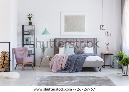 Comfortable powder pink chair next to shelf with firewood in soft pastel bedroom with decorative glass vases