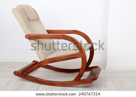 Comfortable rocking-chair on wooden floor near brick wall background - stock photo