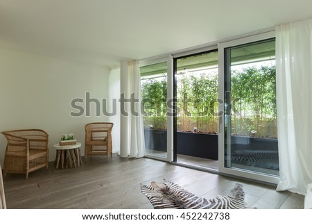 comfortable room with balcony, curtains on the windows - stock photo