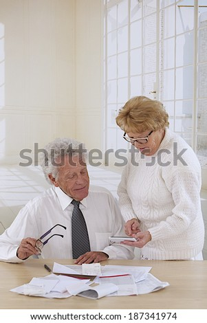 comfortable senior couple at home organizing  bills and administrative paper   - stock photo