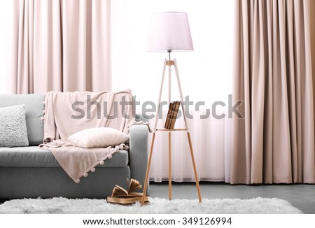 Comfortable sofa with lamp and book against window in the room - stock photo