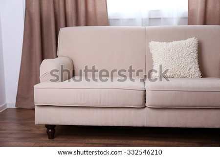 Comfortable sofa with pillows in the room, close up