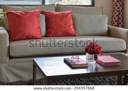 comfortable sofa with red pillows and red book on wooden table in living area at home