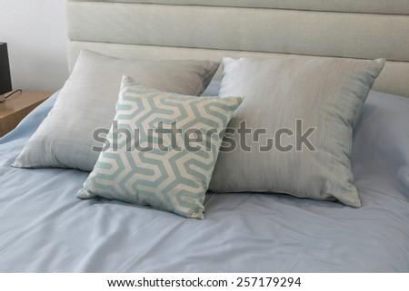 Comfortable soft pillows on the light blue bed and decorative table lamp - stock photo