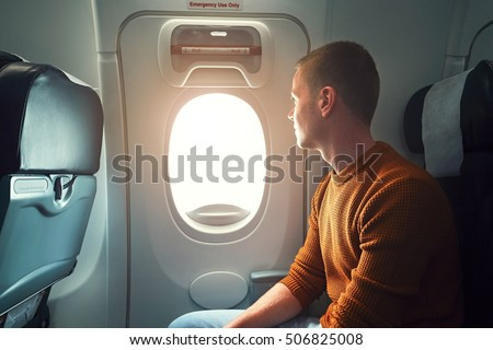 Comfortable traveling by airplane. Curious young passenger looking from the window. - selective focus