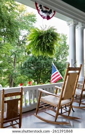 Comfortable wooden rocking chair on an outdoor patio with an ornamental white balustrade below the Stars and Stripes American flag to enjoy 4th July and Independence Day - stock photo