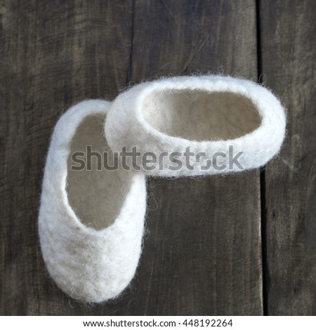 Comfortable wool home Baby Booties on wooden background - stock photo