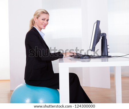 Comfortable working environment with an elegant young blonde office worker sitting on a pilates ball - stock photo