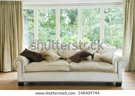 Comfy sofa with cushions against glass windows in the living room - stock photo