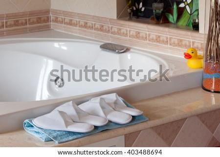 Comfy spa-style slippers near jacuzzi bathtub in home bathroom. - stock photo