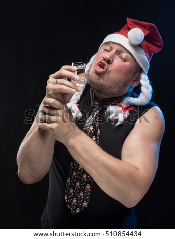 Comic actor man in cap with braids with a glass of vodka on a black background, in anticipation of Christmas and New Year