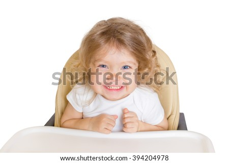 Comic happy smiling baby in the high chair. Kid waiting for favorite baby food or full-fed. Isolated on white background.