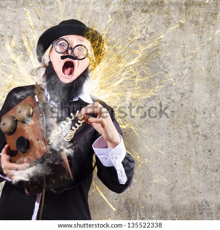 Comic portrait of a shocked business man getting zapped by electrical current charge from vintage telephone - stock photo