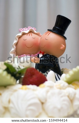 Comical bride and groom figurines on top of wedding cake - stock photo