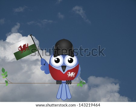 Comical Welsh flag waving bird Patriot sat on a tree branch against a cloudy blue sky