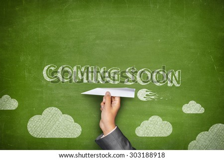 Coming soon concept on green blackboard with businessman hand holding paper plane - stock photo