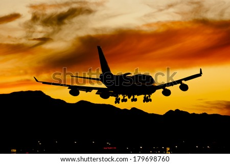 Commercial aircraft land at an airport at sunset - stock photo