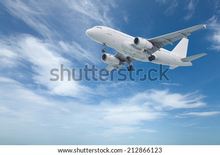 Commercial airliner before landing flying above with blue sky in background