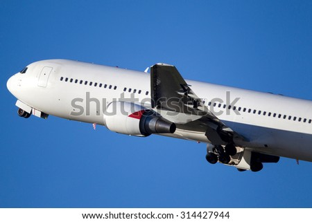 Commercial airliner climbs into the blue sky