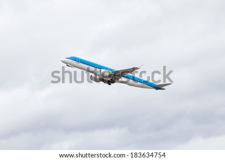 Commercial airliner flying midair after takeoff with the landing gear and wheels still extended as it climbs for height against a blue sky, conceptual of air travel - stock photo