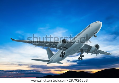 Commercial airplane flying at sunset - stock photo