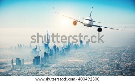 Commercial airplane flying over modern city - stock photo