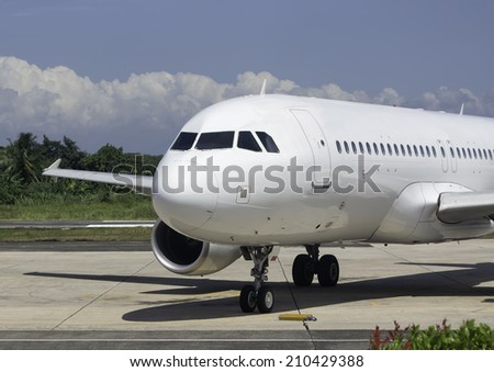 Commercial airplane on tarmac waiting to be serviced by ground crew - stock photo