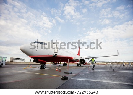 Commercial Airplane On Wet Runway Against Cloudy Sky