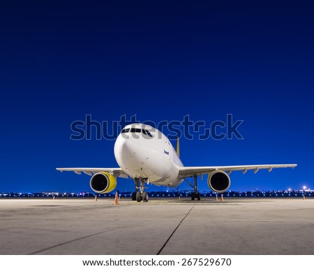 Commercial airplane parking at night - stock photo