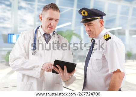 Commercial airplane pilot with doctor  - stock photo