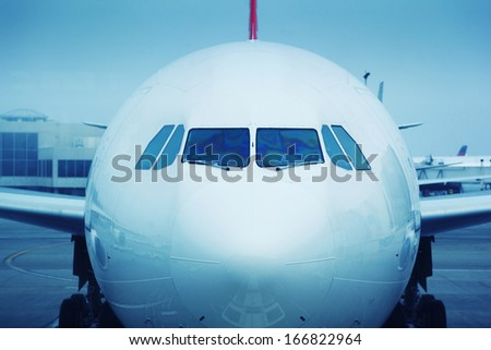 Commercial airplane plane in airport, cockpit front view. - stock photo