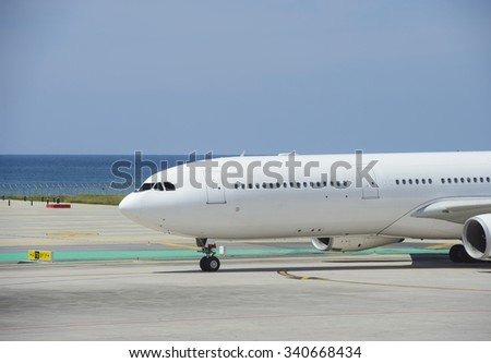 Commercial airplane taxiing on a seashore - stock photo