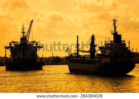 Commercial cargo ships at sunset sailing on a bay - stock photo