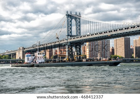 Commercial cargo vessel ship at Eat River in New York City under Manhattan Bridge