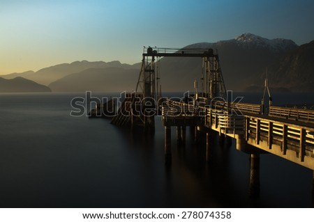 Commercial dock in lake at dawn with mountains in the background - stock photo