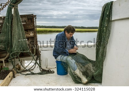 Commercial fisherman mends his net on the deck of a boat - stock photo
