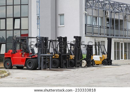 Commercial forklifts in front of distribution warehouse - stock photo