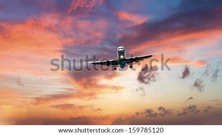 commercial jet airplane in flight at sunset - stock photo