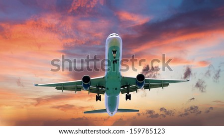 commercial jet airplane in flight at sunset