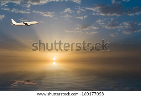 commercial jet airplane in flight at sunset above the sea - stock photo