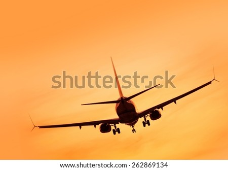 Commercial Passanger Airplane Landing at Sunset.  - stock photo