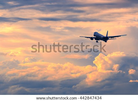 Commercial passenger airplane coming in for landing against beautiful colorful sunset, color and contrast enhanced