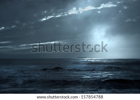 Commercial ships crossing the Portuguese coast at sunset with interesting light and sunbeams; toned blue - stock photo