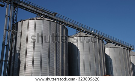 Commercial Steel Grain Silos. Steel Silos and Bins for Grain Storage. Row of steel grain silos used to store agricultural products. - stock photo