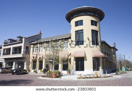 commercial strip mall with circular corner tower and striped awnings - stock photo