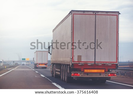 Commercial trailer truck in motion on freeway on cloudy autumn afternoon, cargo transportation.